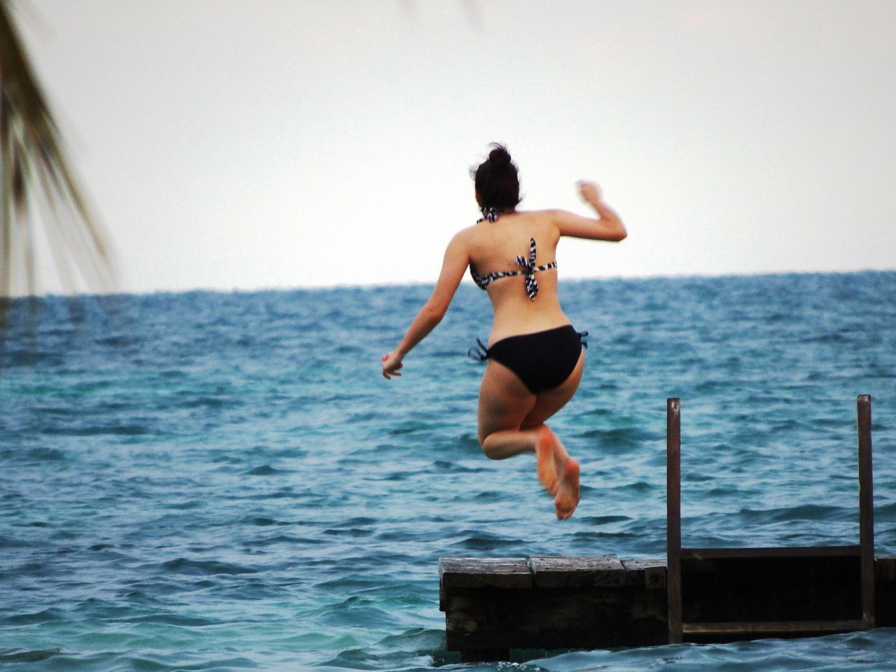 Guest jumping off dock at St George's Caye Resort Belize